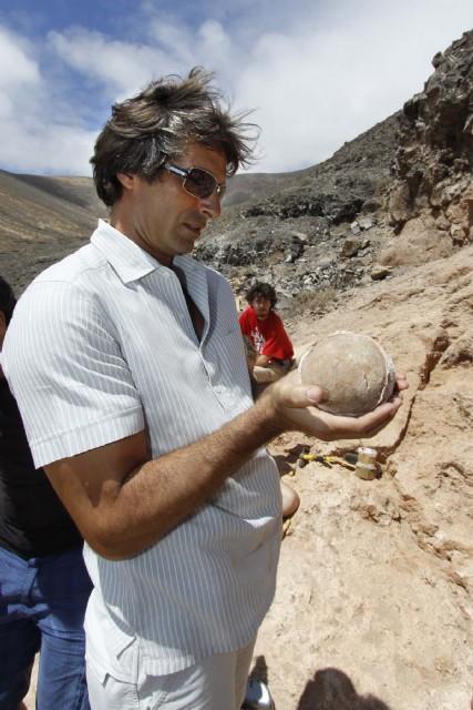 Pedro San Ginés sosteniendo uno de los restos en el yacimiento de Órzola. Fuente: Cabildo de Lanzarote